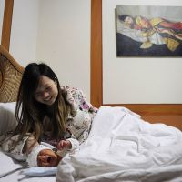Joys of motherhood: A new mother smiles at her baby on a bed in a maternity ward at Beijing Antai Hospital. | AFP-JIJI