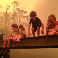 Just in time: Liam Walker, 9, prepares to leap into the water with his siblings (from left) Caleb, 6, Esther, 4, and Matilda, 11, seen holding 2-year-old Charlotte, to take refuge under a jetty from wildfires in the Tasmanian town of Dunalley, Australia, on Jan. 4. | AP
