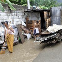 Overwhelmed: An East Timorese couple clean the yard outside their hut in Dili on Jan. 2, after heavy rains flooded the city. The tiny half-island nation is struggling with widespread poverty and a laggard economy, despite offshore energy reserves worth billions of dollars and a steady stream of aid into Asia's newest nation. | AFP-JIJI