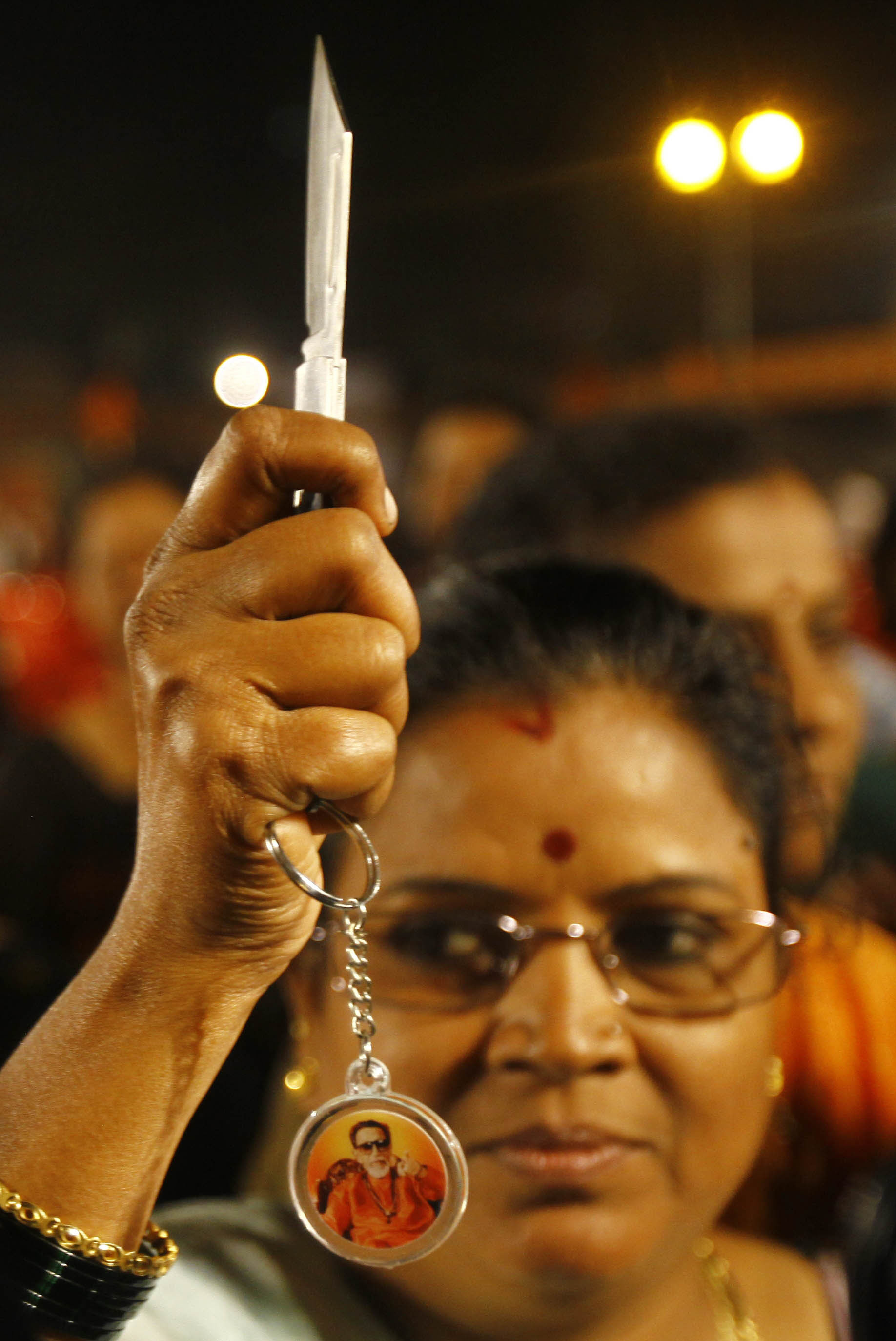 Knife fight: A woman holds up a knife she received after they were distributed by Shiv Sena party leaders in Mumbai on Wednesday. Local news reports said party leaders distributed the knives to women for self-defense during an event to mark the birthday of party founder Bal Thackeray, who died last year. | AP
