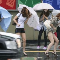 Windswept: Trying to keep your hair looking good in the face of a summer typhoon is enough to depress any girl. | KYODO