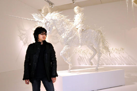 Powerful procession: Motohiko Odani cuts a rock-starlike figure in front of one of his recent sculptures, 'Hollow: What rushes through every mind,' at his new solo exhibition at Tokyo's Mori Art Museum. | SATOKO KAWASAKI PHOTOS