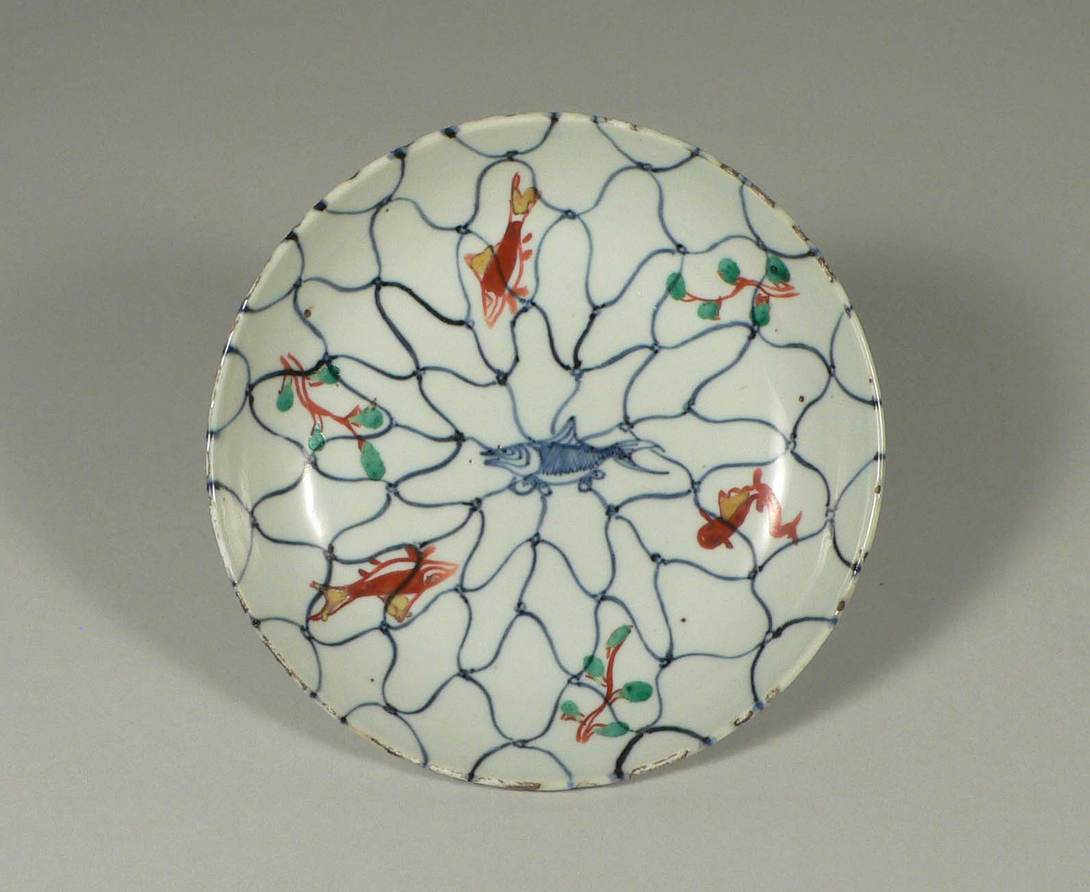 'Porcelain Dish with Fish and Water Plants against an Overall Fishnet Design in Underglaze Blue and Overglaze Enamels' (Ming Dynasty, 17th century) | GIFT OF MR. MIKIO HORIO