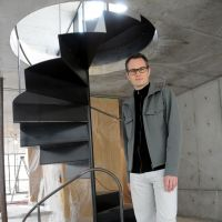Florian Busch poses by a spiral staircase, one of the features of his Tokyo-based architectural company's first project, a residence in Takadanobaba, Shinjuku. | SATOKO KAWASAKI PHOTO