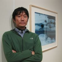 More than a simple snapshot: Tomoki Imai, standing in front of one of his photographs at the Meguro Museum of Art, says he maps visual experiences and captures moments. | KEN KAWASHIMA