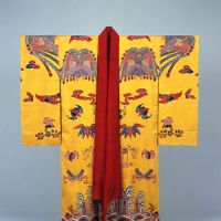 Royal threads: A designated national treasure bingata (Ryukyuan resist-dyed)costume decorated with Chinese phoenixes, bats and waves on a yellow background. (18th-19th century). | NAHA CITY MUSEUM OF HISTORY