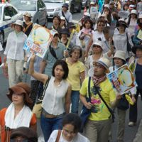 Artist expression: Antinuclear protesters at a rally hold up banners with an image of Yoshitomo Nara's 'No Nukes Girl' | MIO YAMADA