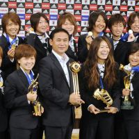 Golden girls: Nadeshiko Japan, with head coach Norio Sasaki (center) and captain Homare Sawa (center right), show off their Women's World Cup trophies. | KYODO PHOTO