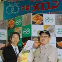 Strange fruit: Yubari Mayor Naomichi Suzuki presents Kazuo Watari, manager of Kurashige Shoten grocery, with two melons for which Watari bid ¥1 million. | KYODO