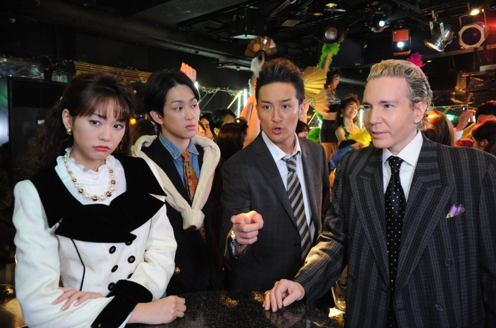 Back to the bubble: From left, Mirei Kiritani as Shoko Mano, Yu Yokoyama as Kiyofumi Takano, Masahiro Matsuoka as Teppei Kogure and guest star Dave Spector in a flashback scene from TV Asahi's '13-sai no Hello Work.' | TV ASAHI
