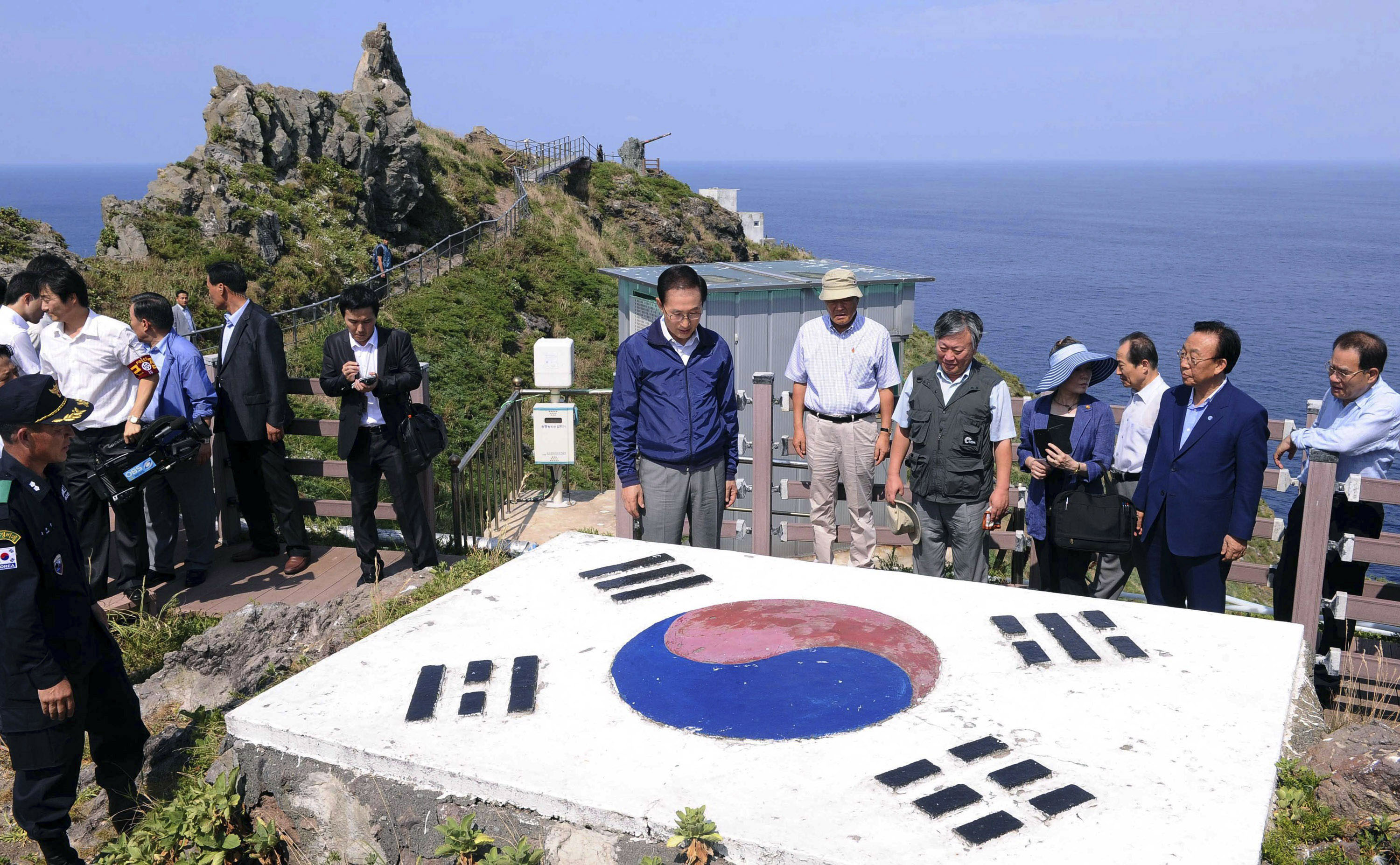Flag waving: South Korean President Lee Myung Bak (left) during a surprise visit Aug. 10 to the disputed islands called Dokdo in Korea and Takeshima in Japan. | AP