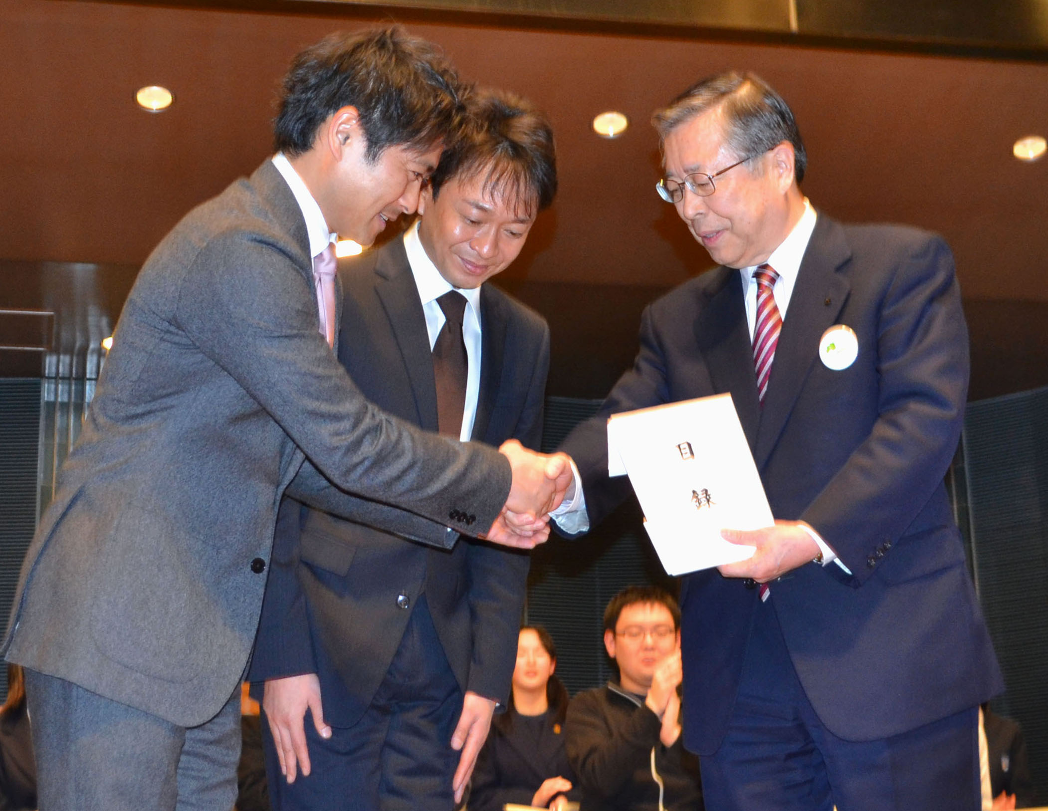 Idol hands make right: Tatsuya Yamaguchi (left) and Shigeru Joshima (center) of the pop group Tokio present Fukushima Prefectural Gov. Yuhei Sato (right) with a donation to aid the disaster-stricken prefecture. | KYODO