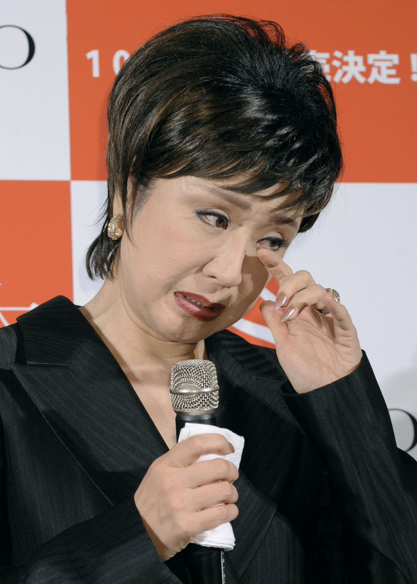 Red, white and blue: Enka singer Sachiko Kobayashi tears up during a recent press conference. The singer caused controversy in the spring by sacking two longtime employees of her production company, Sachiko Promotion. | KYODO