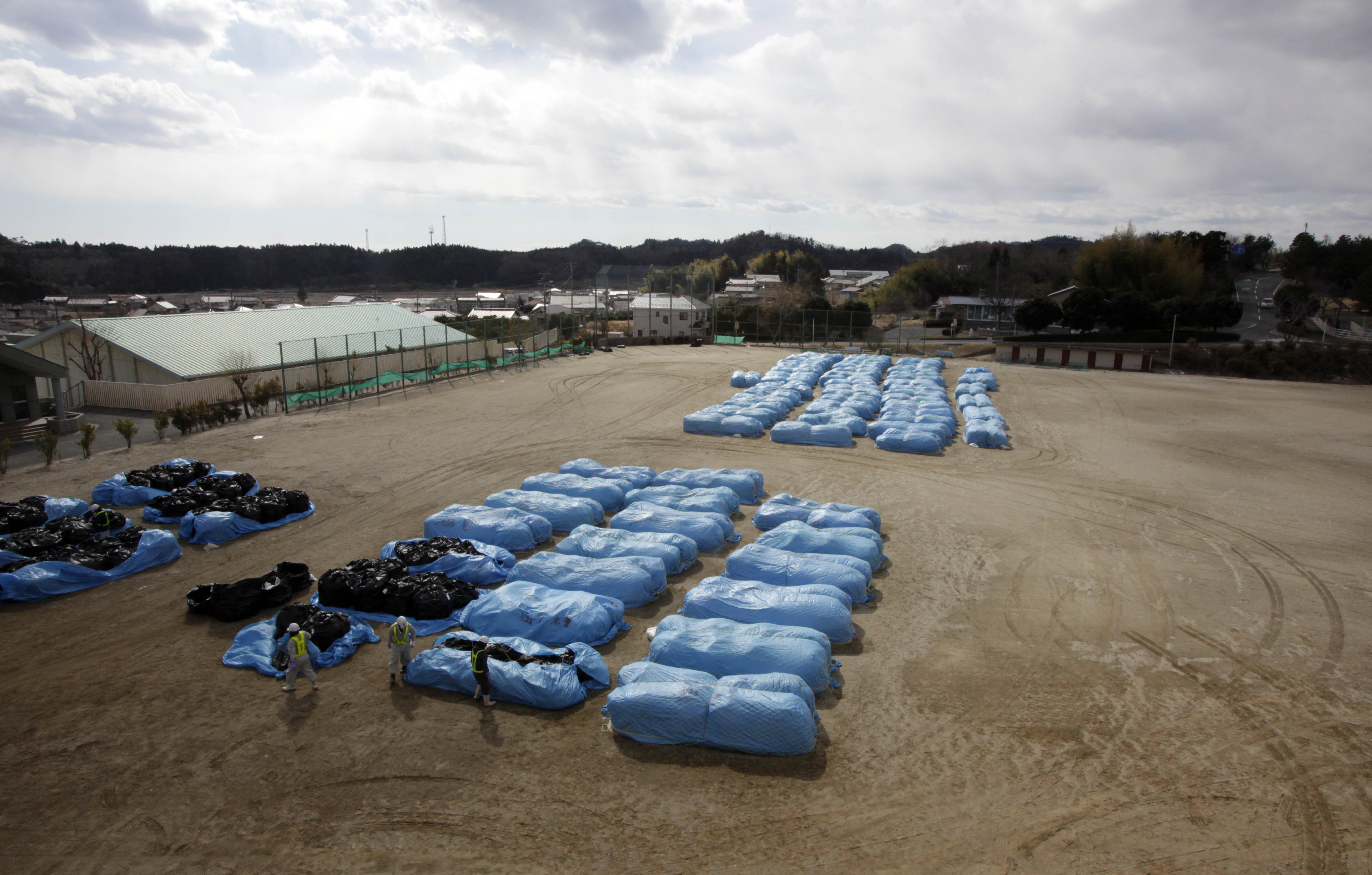Cleaning up: Workers at a school sports field in Hirono, outside the Fukushima nuclear exclusion zone, prepare bags of radiation-contaminated earth for shipment to a dumping ground. | AP