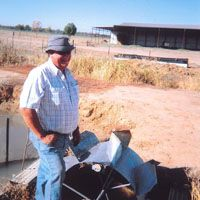 An outback farmer stands beside an early 20th-century Dethridge water-wheel