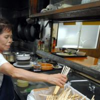 Wood you believe it?: A worker at the Shokudo Shogetsu restaurant in Tamachi, Tokyo, adds to the diner's daily tally of single use waribashi chopsticks. | YOSHIAKI MIURA PHOTO