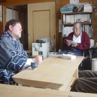 Honored guest: C.W. Nicol with Ainu leader Shigeru Kayano at his home in Nibutani, Hokkaido, on Jan. 17, 2006, after being presented with this embroidered Ainu kimono. | NATSUYO SEARLE PHOTO