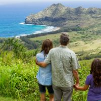 Family ties: Royal descendant Matt King (George Clooney) stands with daughters Alexandra (Shailene Woodley, left) and Scottie (Amara Miller, right) and looks over a piece of land he owns on the Hawaiian island of Kauai. | © 2011 TWENTIETH CENTURY FOX