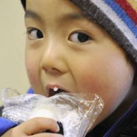 Savor the flavor: A young boy at an evacuation center set up for victims of the Mount Shinmoe volcanic eruption in Miyazaki Prefecture, which occurred earlier this year, tucks into an onigiri (rice ball) prepared by volunteer workers. | KYODO PHOTO