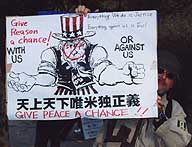 A disguised demonstrator holds a sign at last year's antiwar protest in Hibiya Park.