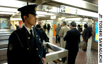 A Police officer stands guard at Shinbashi station in Tokyo in March. More police have been deployed in train stations and transport hubs as fears of a terrorist attack increase.