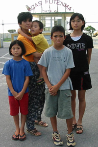 Kuba Tatsuno stands with her children the Futenma base.