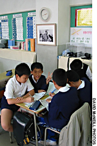 Children take classes (above) at Kanagawa Korean School, Which receives theatening calls most days and whose students have suffered beating and knife attacks, according to headmaster Yu Ze Song.