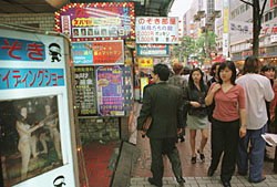 Peep-show signs beckon customers in Tokyo's Kabukicho area. Japan's thriving sex trade has made the country a haven for sex trafficking. | AP PHOTO