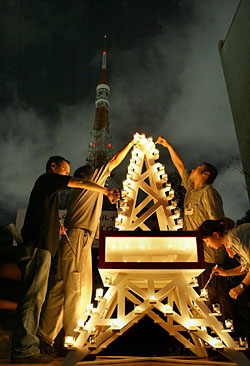 PEOPLE LIGHT CANDLES near a darkened Tokyo Tower to raise awareness of energy saving.The Japan Productivity Center has calculated twould save 40 tons of carbon dioxide emissions daily. | AP PHOTO