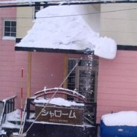 A man clears snows off the roof of his pension in Niseko. | AMY CHAVEZ PHOTO
