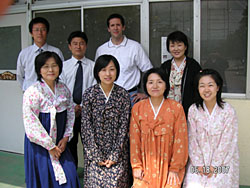 Teacher Jason Williams poses with coworkers at Okayama Korean Primary and Middle School, and institution for Korean residents of Japan supported by funding from North Korea. Female staff and students at the school wear the traditional Korean 'chima chogori.' | JASON WILLIAMS PHOTO