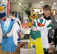 A staffer at the Cosmint shop for cosplayers in Tokyo's Nakano Ward displays some of the hundreds of not-inexpensive costumes available for those wishing to embody anime, manga or video-game characters. | ERIKO ARITA PHOTO