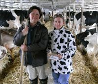 Mrs. Takahashi leans on a fork in her Hokkaido dairy farm while the writer tries to blend in with the barn's residents. | PAUL HOOGLAND PHOTO