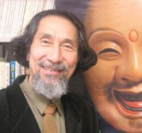 Kansai University Sociology Professor Yoji Kimura (above) smiles in his office beside a poster of Fuku-no-kami (the God of Happiness), and examines one of his computerized Laughogram readouts (below). | TOMOKO OTAKE PHOTOS