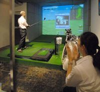 Tee time: A Shirokane Club 'caddy' applauds a patron's drive down the golf bar's virtual fairway. | YOSHIAKI MIURA PHOTO