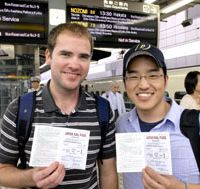 Into the storm: Corey Pederson (left) and Mike Kim disembark in Tokyo (top), the halfway point in their attempt to break the Guinness world record for the furthest distance traveled by train in 24 hours, and displaying their overworked JR rail passes (above) before setting off on the fateful Kyushu-bound leg of their journey (below) during which deluges swamped their record attempt (bottom). | YOSHIAKI MIURA PHOTO; EDAN CORKILL (bottom)