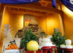 Happy Hotei: New Year's offerings of rice cakes and Mandarin oranges are piled before a statue of Hotei, the joyful god of abundance and good health, at Shusei-in temple in Nishi Nippori in Tokyo's Arakawa Ward. | YOSHIAKI MIURA PHOTO