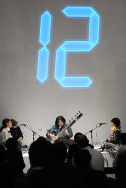Catch the beat: Daikichi Yoshida plays the sitar at 'MAMC Night,' a members' event held Jan. 20 at the Mori Art Museum in Tokyo's Roppongi. Numbers projected on the wall help the audience learn the beat pattern for the clapping accompaniment. | YOSHIAKI MIURA PHOTOS