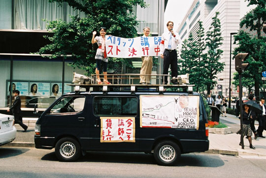 Van hailing: Members of the Berlitz General Union Tokyo (Begunto) and the National Union of General Workers (NUGW) Tokyo Nambu make their voices heard atop a sound truck outside the Berlitz school in Yurakucho, Tokyo. | COURTESY OF BEGUNTO