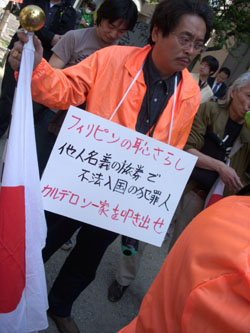 A rightwing protester holds a Hinomaru flag at the protest.