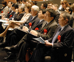 Judges with red roses on their lapels listen intently to the speeches.