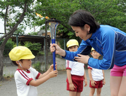 A Kobato Nursery school pupil receives the torch from Mongolian volunteer Baast Burmaa to then make a wish for peace.