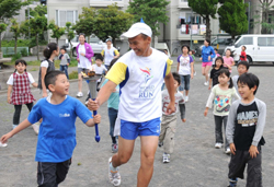 Charity run: Mongolian runner Akanola Tsogtbaantar Norov (left photo) jogs around the playground at Iwase Kodomo Kaikan in Kamakura, Kanagawa Prefecture, earlier this month holding the torch with a boy.
