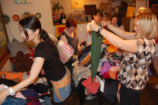 Check it out: Women hunt through piles of clothes at the charity clothes swap at Tokyo's Pink Cow art bar and restaurant. The ladies-only event is a boon to foreigners, who often have difficulty finding the styles and sizes they need in Japan. To top it off, the price is right. A 2,500 yen door charge covers whatever can be carried home. | KAZUAKI NAGATA PHOTOS