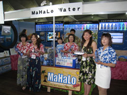 The Aloha Yokohama event held July 22 to 26 featured various shops and performances. (Above) Women pose in a booth selling bottled water from Hawaii, while girls dance hula in front of visitors at the Osanbashi Pier venue. | MINORU MATSUTANI PHOTOS
