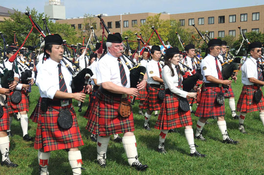 Strains of home: Bagpipers, including piping judge Iain MacDonald (second from left), march in the opening parade. | SATOKO KAWASAKI PHOTOS