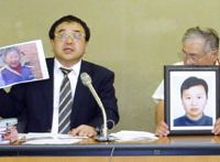 Worked to death: At a news conference in Tokyo a year ago, lawyer Shoichi Ibusuki holds up a photo of one of the daughters of Chinese trainee Jiang Xiaodong (in the framed picture right). The cause of Jiang's death in 2008 was recognized as karoshi by the Kashima Labor Standards Inspection Office last month. | KYODO PHOTO