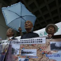 Unpaid dues: Elderly Chinese forced to work in Japanese mines during World War II call for compensation in front of the head office of Mitsubishi Electric Hong Kong Group Ltd. in the Chinese territory last week. | AP PHOTO