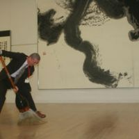 Mr. Big: Artist and teacher Rebun Matsuzaki demonstrates the dance-like process by which he created the giant work hanging behind him in the Dokuritsu Shojindan Foundation's exhibition of shodo (Japanese calligraphy) now at the National Art Center, Tokyo. | EDAN CORKILL PHOTOS