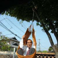 Hanging around: Professor Shigeyoshi Osaki demonstrates the strength of spider silk by swinging in a hammock supported by threads he harvested. | SHIGEYOSHI OSAKI PHOTO